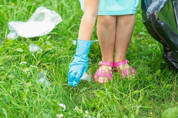 Kleines mädchen reinigt plastikmüll auf dem grünen gras im park