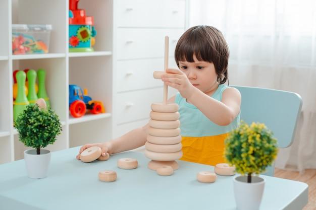 Kleines mädchen sammelt eine unbemalte holzpyramide. sicheres kinderspielzeug aus naturholz.