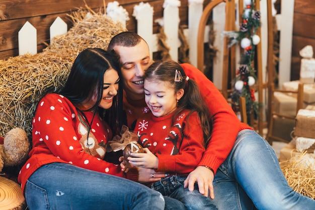 Kleines mädchen schaut die lustige aufstellung mit ihren eltern auf dem heu in einem weihnachtsstudio
