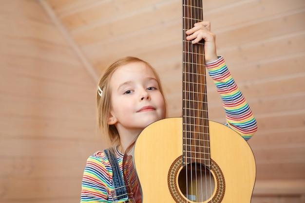 Kleines mädchen schaut zu hause hinter einem gitarrenkoffer hervor.
