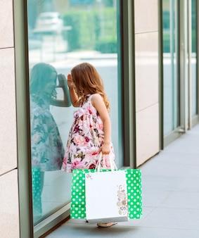 Kleines mädchen schaut zum fenster in der nähe des einkaufszentrums.