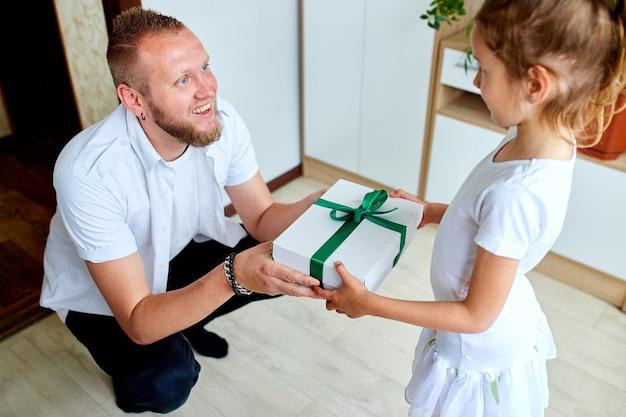 Kleines mädchen schenkt ihrem hübschen vater am vatertag eine geschenkbox, lächelnde tochter, die papa gratuliert und zum geburtstag zu hause ein geschenk gibt. ich liebe dich papa. alles gute zum vatertag.