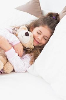 Kleines mädchen schlafend mit teddybären