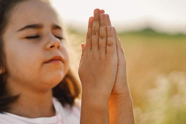 Kleines mädchen schloss die augen und betete in einem feldweizen. hände im gebet gefaltet. religionskonzept
