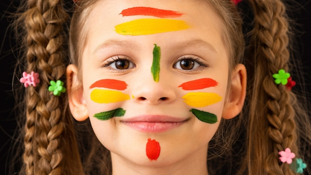 Kleines mädchen schmierte ihre hände und ihr gesicht mit farbe.