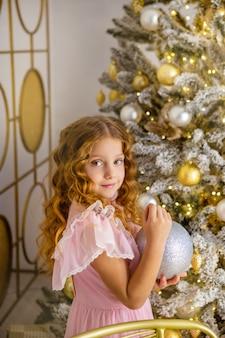 Kleines mädchen schmücken den christmassenbaum, neujahrskonzept. kind nahe weihnachtsbaum, mädchen im rosa kleid.