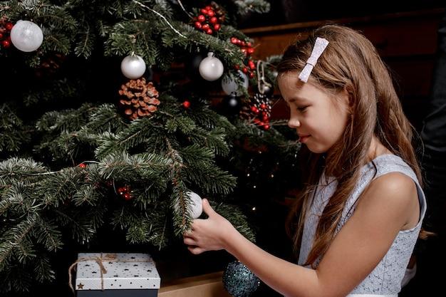 Kleines mädchen schmückt den weihnachtsbaum im wohnzimmer zu hause