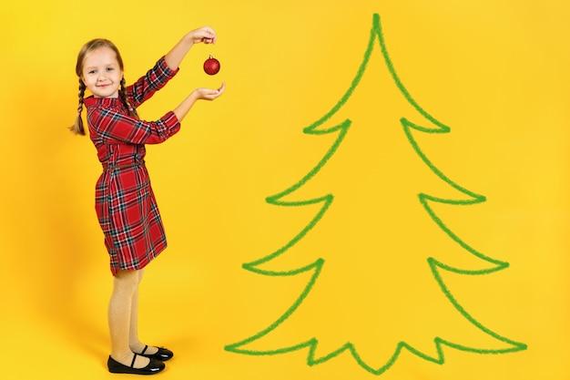 Kleines mädchen schmückt einen weihnachtsbaum.