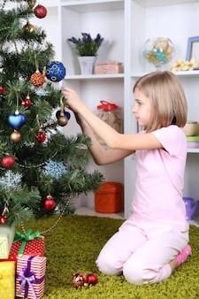 Kleines mädchen schmückt weihnachtsbaum im zimmer