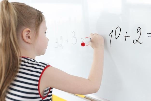 Kleines mädchen schreibt mathebeispiele auf whiteboard Premium Fotos