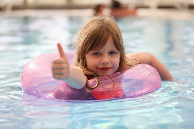Kleines mädchen schwimmt im pool mit aufblasbarem kreis und zeigt daumen nach oben