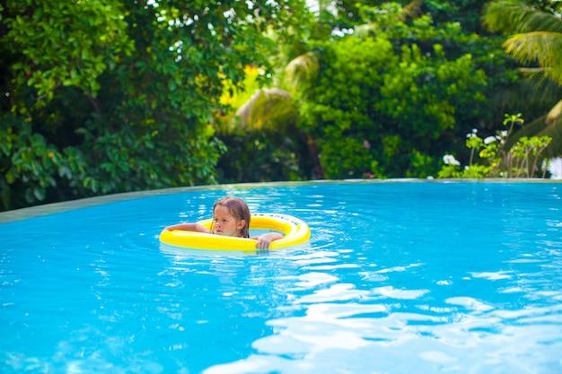Kleines mädchen schwimmt in einem gummiring am pool