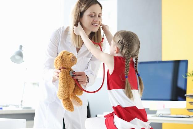 Kleines mädchen setzt stethoskop auf kinderarzt. doktor hält stofftier. pädiatrie arbeiten mit kindern konzept