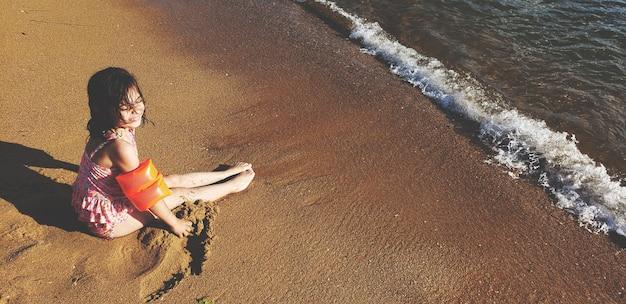 Kleines mädchen sitzen am strand