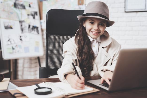 Kleines mädchen sitzt am schreibtisch und macht sich notizen in der nähe von laptop.