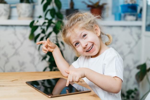 Kleines mädchen sitzt an einem tisch mit einer tablette mit erhobenen händen lächelnd und glücklich