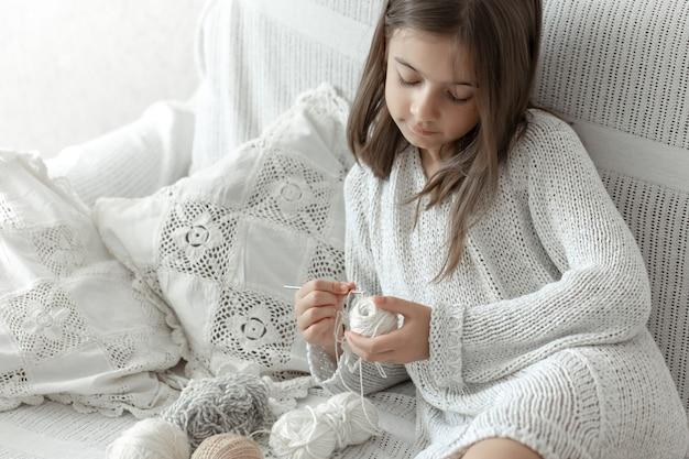 Kleines mädchen sitzt auf dem sofa mit fäden, heimfreizeitkonzept, häkeln.