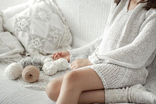 Kleines mädchen sitzt auf dem sofa mit fäden, heimfreizeitkonzept, stricken.