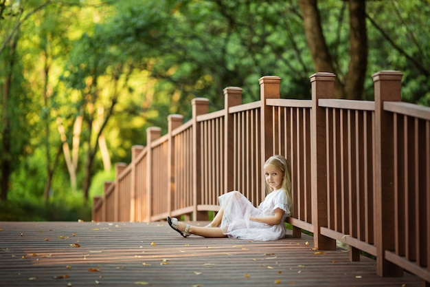 Kleines mädchen sitzt auf der brücke im park
