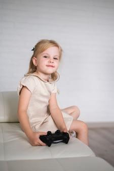 Kleines mädchen sitzt auf der couch mit joystick