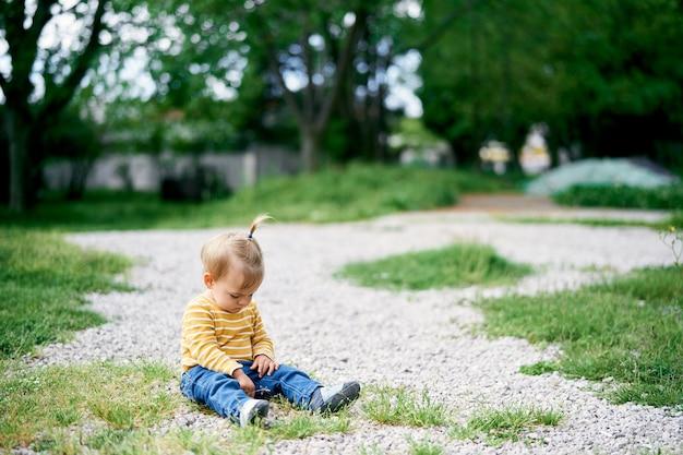 Kleines mädchen sitzt auf einem kiesweg im park und senkt den kopf