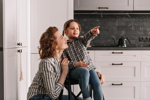 Kleines mädchen sitzt auf einem stuhl und zeigt mit dem finger zur seite. mutter und tochter posieren in der küche.