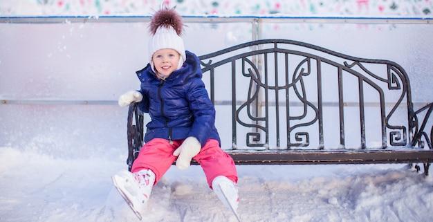 Kleines mädchen sitzt auf einer bank in der eisbahn