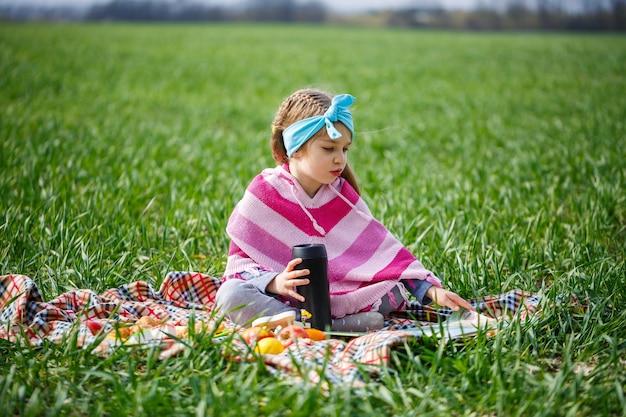 Kleines mädchen sitzt auf einer tagesdecke und liest ein buch mit einem märchen, grünes gras auf dem feld, sonniges frühlingswetter, lächeln und freude des kindes, blauer himmel mit wolken