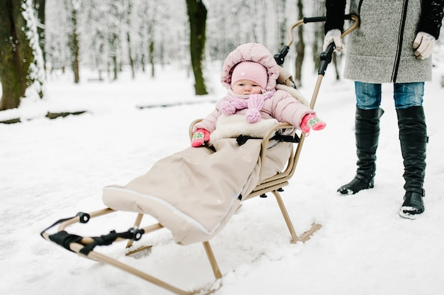 Kleines mädchen sitzt im schlitten im park. nahansicht. glückliche familie, die im park spazieren geht.