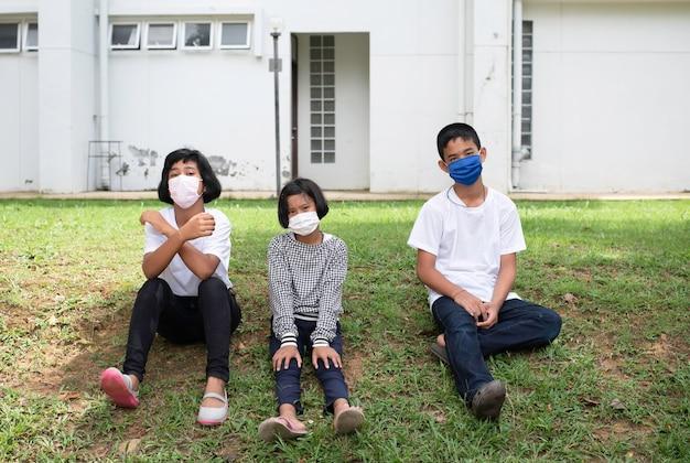 Kleines mädchen sitzt in der mitte der jüngeren schwester und ihres bruders. sie tragen eine maske, um sich vor krankheiten zu schützen, einem neuen normalen leben