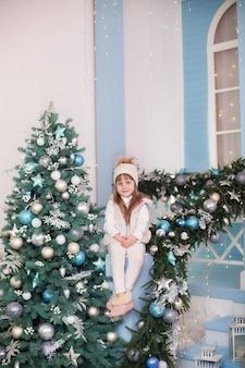Kleines mädchen sitzt in der nähe von weihnachtsbaum auf veranda des hauses