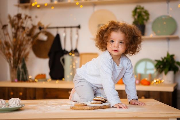 Kleines mädchen sitzt in der weihnachtsküche auf dem tisch