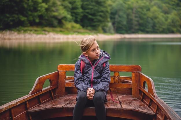 Kleines mädchen sitzt in einem holzboot