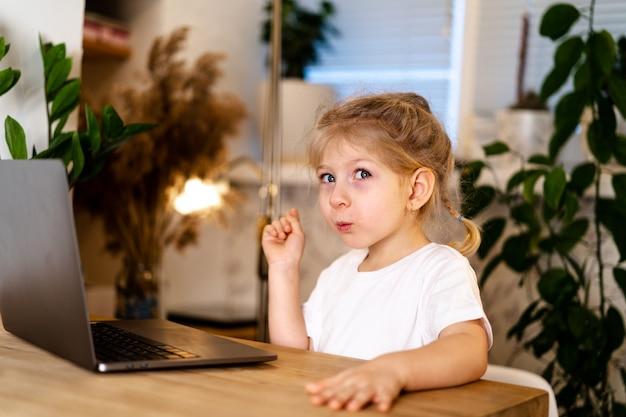 Kleines mädchen sitzt mit erhobenem finger an einem tisch mit einem laptop, lächelt und wird schlau, erlebt