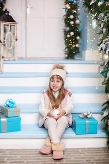 Kleines mädchen sitzt mit geschenken auf der veranda eines hauses, das für weihnachten geschmückt wird