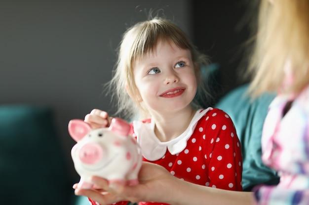 Kleines mädchen sitzt mit ihrer mutter auf der couch und steckt münze ins sparschwein