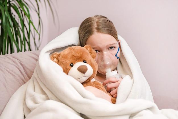 Kleines mädchen sitzt mit spielzeug auf sofa zu hause in einer maske zum einatmen und macht einatmen mit vernebler zu hause inhalator.