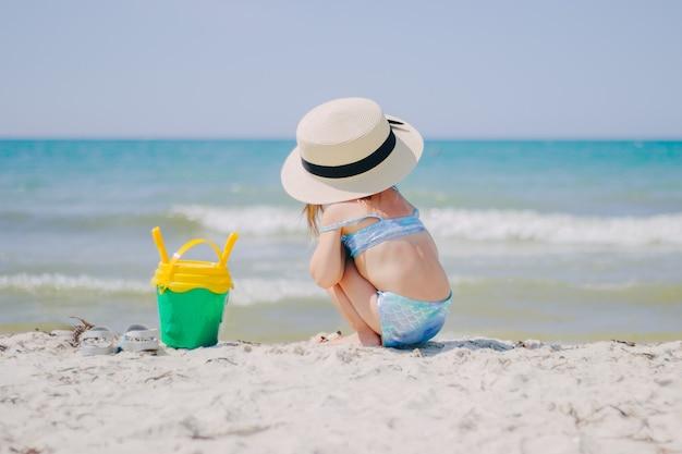 Kleines mädchen sitzt rückwärts am strand in einem strohhut und mit einem eimer sand zum spielen