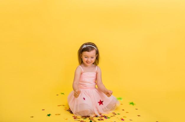 Kleines mädchen sitzt und hält konfetti-sterne auf einem gelben