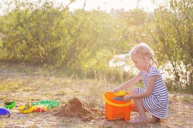 Kleines mädchen spielen auf sand mit spielzeug