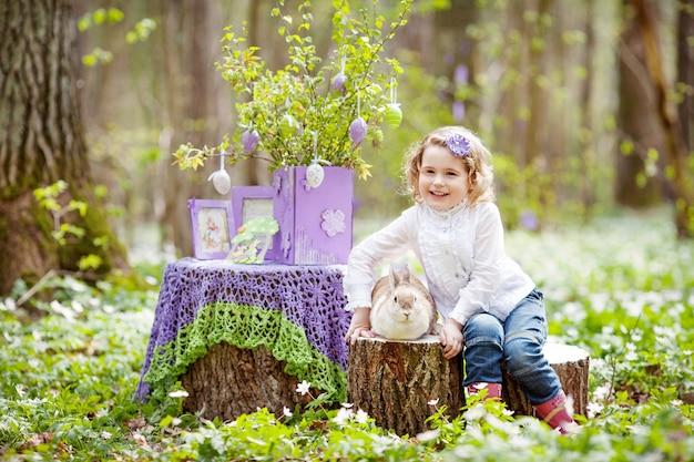 Kleines mädchen spielen mit echtem kaninchen im garten. lachendes kind bei ostereiersuche mit haustierhase. frühlingsspaß im freien für kinder mit haustieren