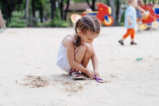 Kleines mädchen spielen sandkasten spielplatz graben sand schaufel gebäude sand figur sommertag. kaukasisches weibliches kind 5 jahre spaß im freien
