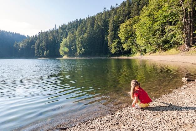 Kleines mädchen spielt am ufer eines bergsees