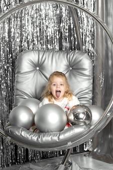 Kleines mädchen spielt auf einem stuhl eine glasschale mit silbernen kugeln