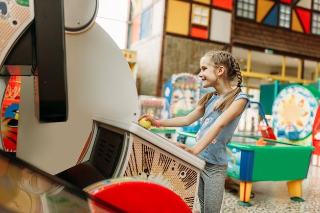 Kleines mädchen spielt auf videospielmaschine