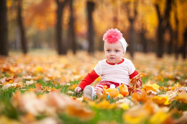 Kleines mädchen spielt im herbstpark mit einem lächeln.