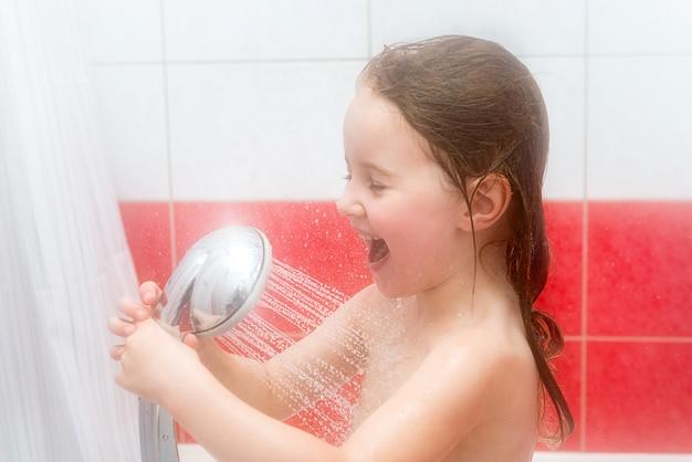 Kleines mädchen spielt in der dusche und lacht