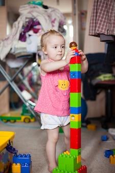 Kleines mädchen spielt mit bunten plastikblöcken in einem wohnzimmer