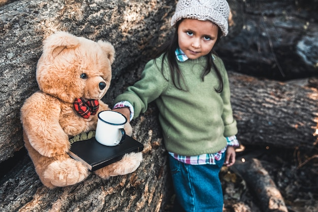Kleines mädchen spielt mit einem bären auf den protokollen.