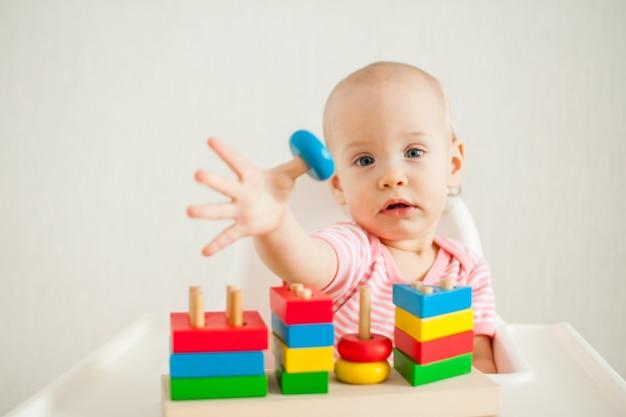 Kleines mädchen spielt mit einem lernspielzeug - einer bunten holzpyramide. entwicklung der geldstrafe